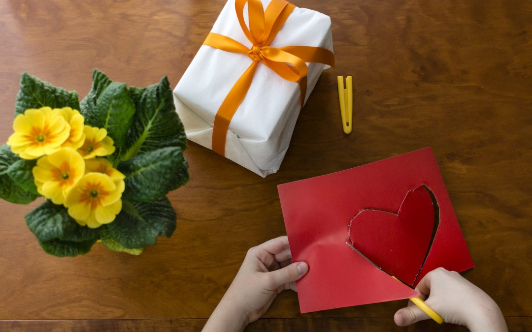 Child cutting out a paper heart to go on a wrapped present