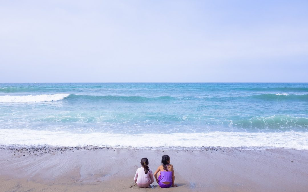 Sea shore with two small girls facing the sea
