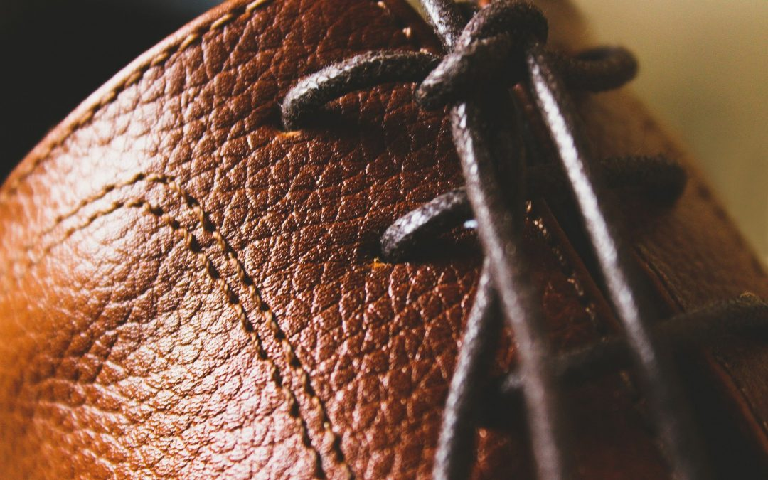 A section of a brown textured leather boot, with laces